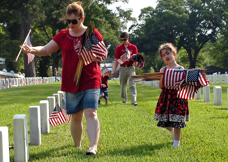 Catherine Gerdes, left, wife of U.S. Marine Master Gunnery Sgt. Timothy Gerdes, who is stationed at Camp Leatherneck in Afghanistan, places United States flags on graves at Alexandria National Cemetery in Pineville, La., Saturday, May 26, 2012, in preparation for Monday's Memorial Day program. The Gerdes' children, Madeline, right, and her brothers Ethan, Colton and Natha help out. (AP Photo/The Daily Town Talk, Melinda Martinez) NO SALES Photo: AP