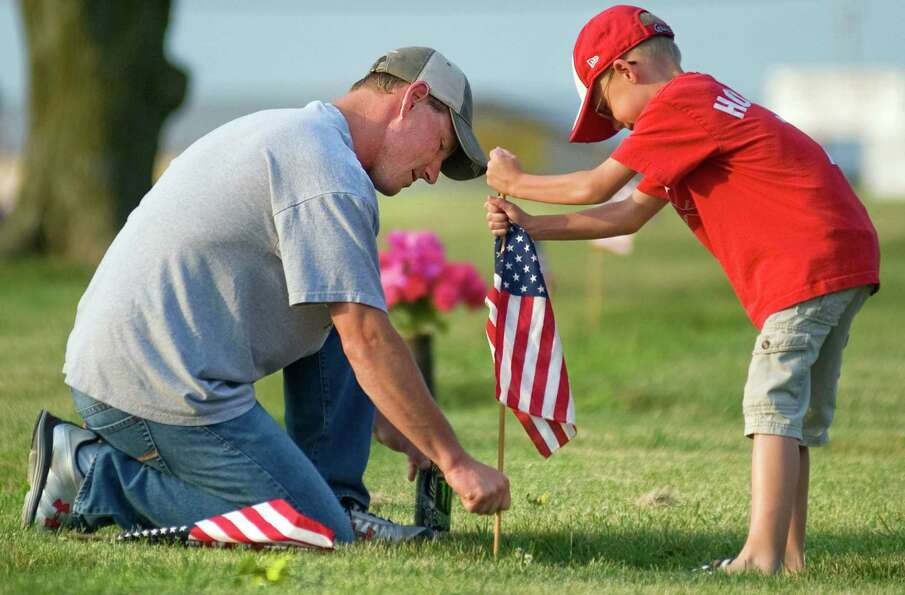 Gage Allison, 7, helps his father, Jason, place a flag at a gravestone of a veteran Saturday, May 26