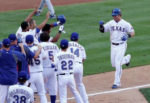 Texas Rangers' Josh Hamilton, right, is greeted at home by teammates following his two-run walkoff home run off Toronto Blue Jays' Jason Frasor in the 13th inning of a baseball game on Saturday, May 26, 2012, in Arlington, Texas. The Rangers won 8-7. Photo: AP