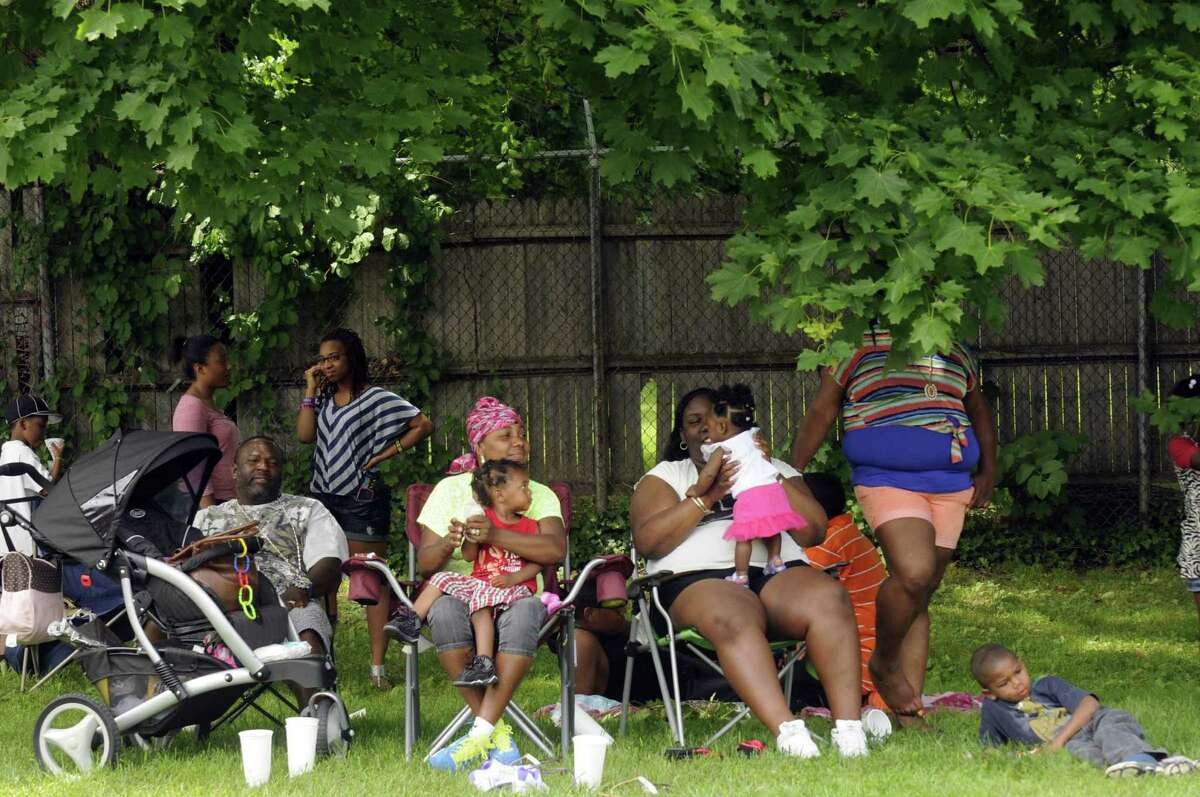 Families sit in the shade and ejoy picnic food and drink during a Safe Summer Picnic sponsored by the Victory Christian Church, Pastor Charlie Muller, District Attorney David Soares and the ENOUGH Program partnered with ShopRite, Albany County Sheriff Craig Apple and the Albany Police Department in memory of the three year anniversary of the death of Katina Thomas at Livingston Park in Albany N.Y. Saturday May 26, 2012. (Michael P. Farrell/Times Union)