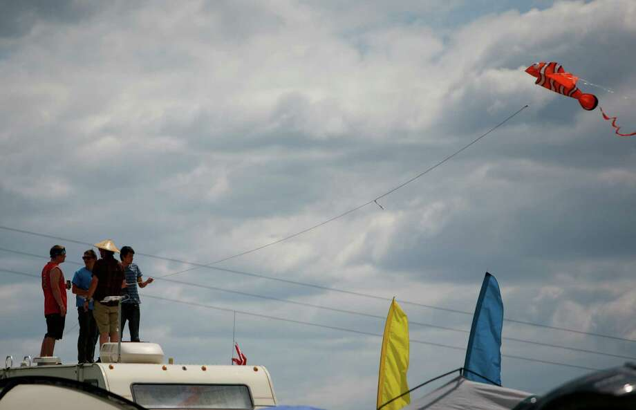 Concert attendees fly a kite while standing on top of their car. Photo: SOFIA JARAMILLO / SEATTLEPI.COM