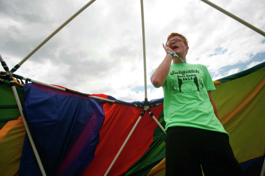 A concert attendee calls a friend over to his hand-made tent at the campground. Photo: SOFIA JARAMILLO / SEATTLEPI.COM