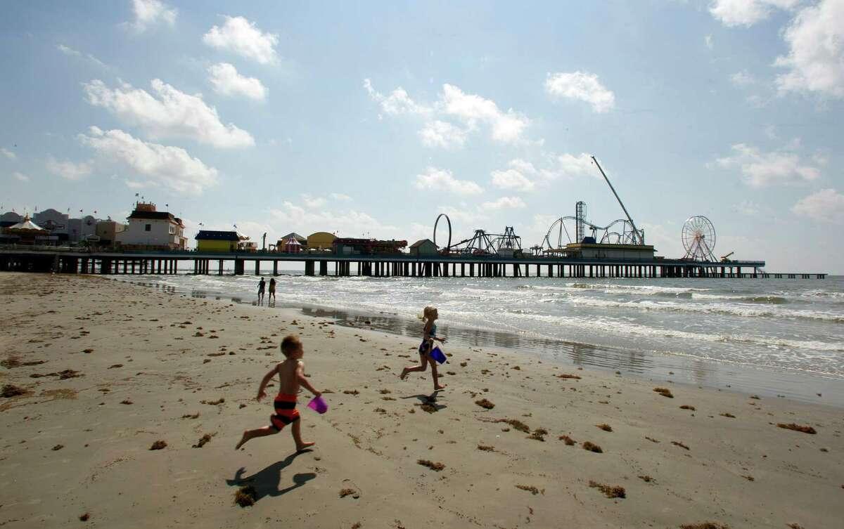 The Pleasure Pier rises down the beach last week as siblings Logan and Emma Graving play near 26th Street.
