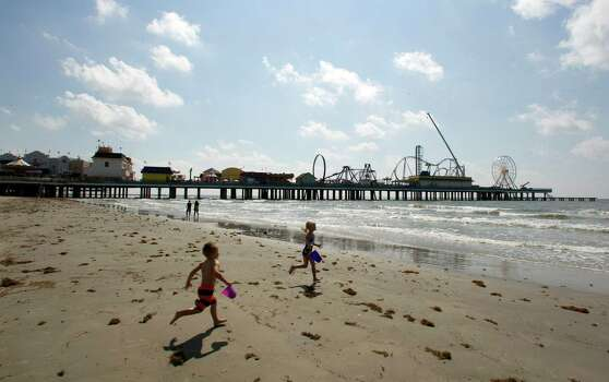 The Pleasure Pier rises down the beach in 2012 as children play near 26th Street. Photo: James Nielsen / © Houston Chronicle 2012