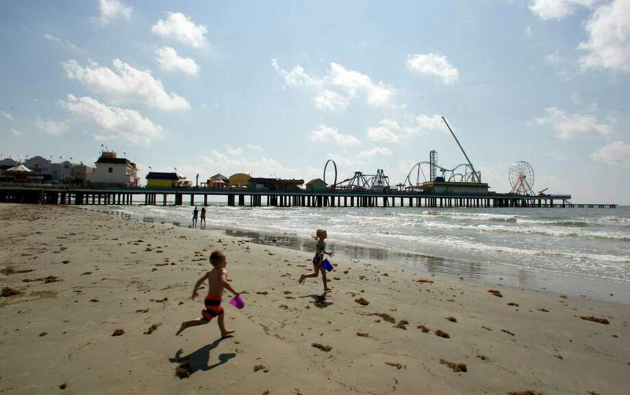 The Pleasure Pier rises down the beach last week as siblings Logan and Emma Graving play near 26th Street. Photo: James Nielsen / © Houston Chronicle 2012
