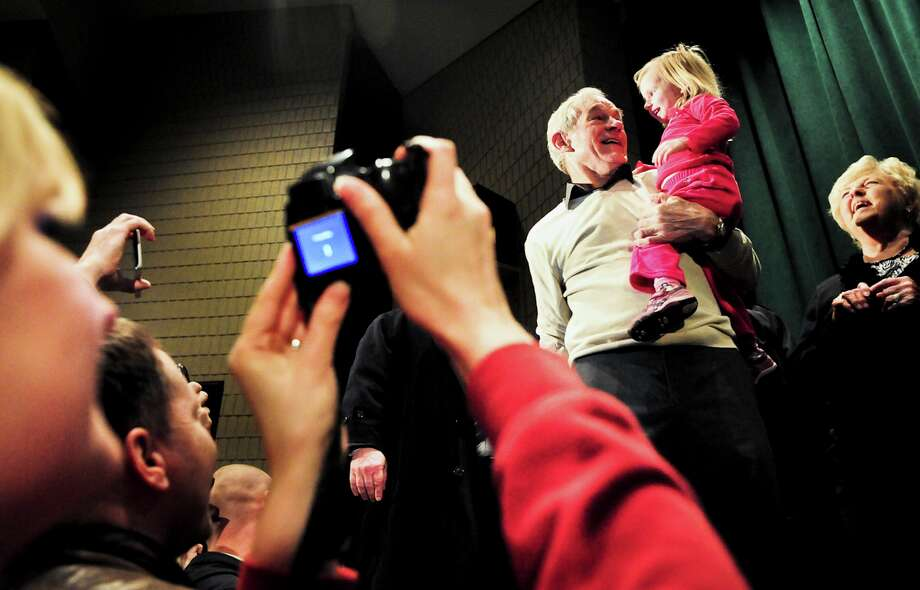 Ron Paul holds Piper DeYoung, 2, during a February campaign stop in Rochester, Minn. Paul's supporters are crashing state GOP conventions around the country to infiltrate the top echelons of the party. Photo: BEN GARVIN / NYTNS