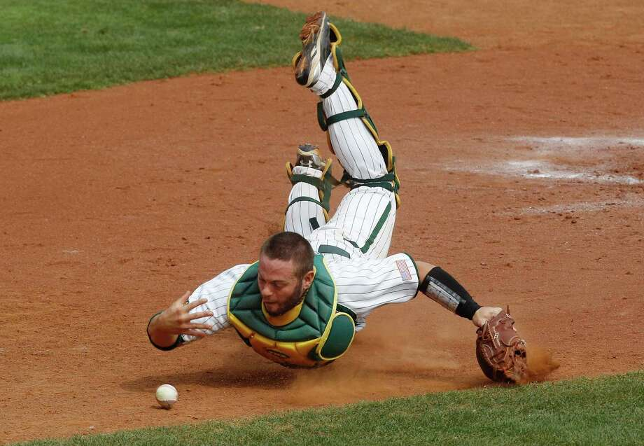 Baylor catcher Josh Ludy can't quite get to a foul ball off the bat of Oklahoma's Jack Mayfield in the fifth inning of the Sooners' win Saturday in Oklahoma City. Photo: Sue Ogrocki / AP