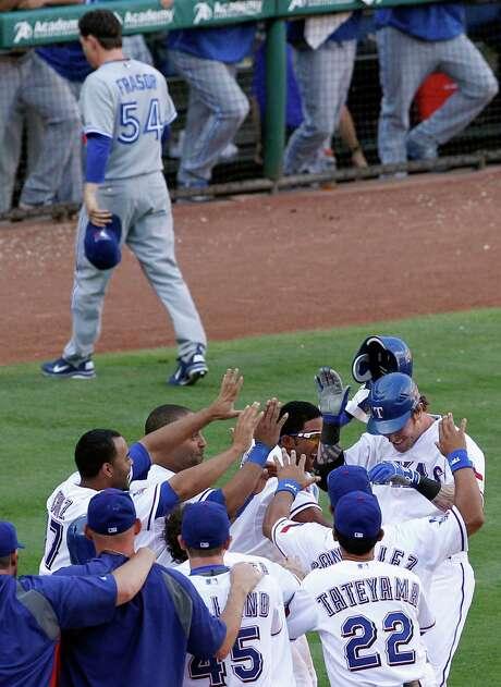 Rangers teammates celebrate Josh Hamilton's 13th-inning, walk-off home run off of Toronto's Jason Frasor (54) as Texas wins in Arlington 8-7. Photo: Tony Gutierrez / AP