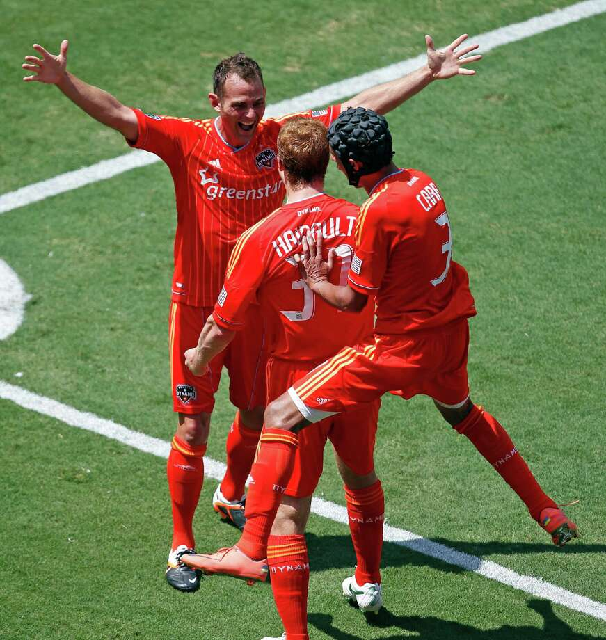 Andre Hainault, center, celebrates with Brad Davis, top, after heading in a corner kick off an assist from Davis in the 57th minute of the Dynamo's win. Photo: James Nielsen / © Houston Chronicle 2012