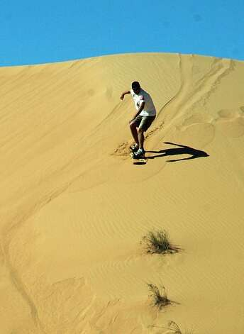 A sandboarder slides down a desert dune outside Dubai. Photo: Bill Fink, Special To The Chronicle