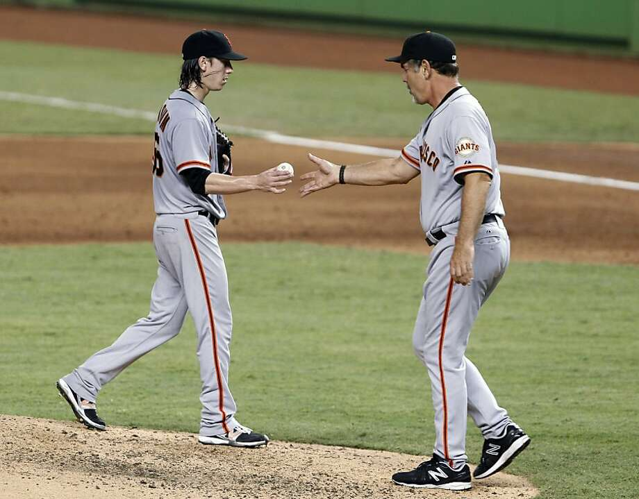 San Francisco Giants starting pitcher Tim Lincecum, left, is taken out by manager Bruce Bochy during the sixth inning of a baseball game against the Miami Marlins, Friday, May 25, 2012 in Miami. The Marlins defeated the Giants 7-6. (AP Photo/Wilfredo Lee) Photo: Wilfredo Lee, Associated Press