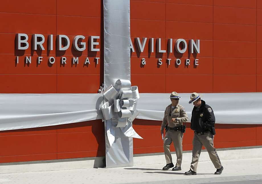 California Highway Patrol officers walk past the new Golden Gate Bridge Pavilion wrapped with a bow for a dedication ceremony in San Francisco, Calif. on Friday, May 25, 2012. The event kicked off a weekend of events to celebrate the iconic bridge's 75th anniversary. Photo: Paul Chinn, The Chronicle
