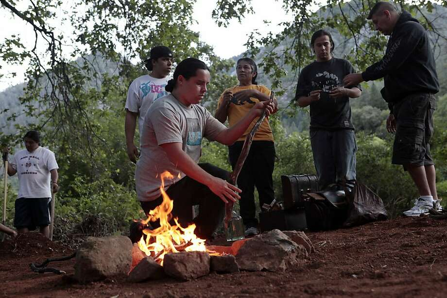 The Winnemen Wintu Tribe Chief Caleen Sisk, center prays as she watches the tribe make a ceremonial fire to prepare for War Dance through the weekend along to waters in McCloud River, to convince the U.S. Forest Services to protect their coming of age ceremony from disruptions and heckling from  boaters, Thursday May 25, 2012, in Redding, Calif. The tribe is planning with the help of volunteers to block a 400-yards stretch of the river. The coming of age ceremony will be held June 29 through July 3 during the next full moon. Photo: Lacy Atkins, The Chronicle