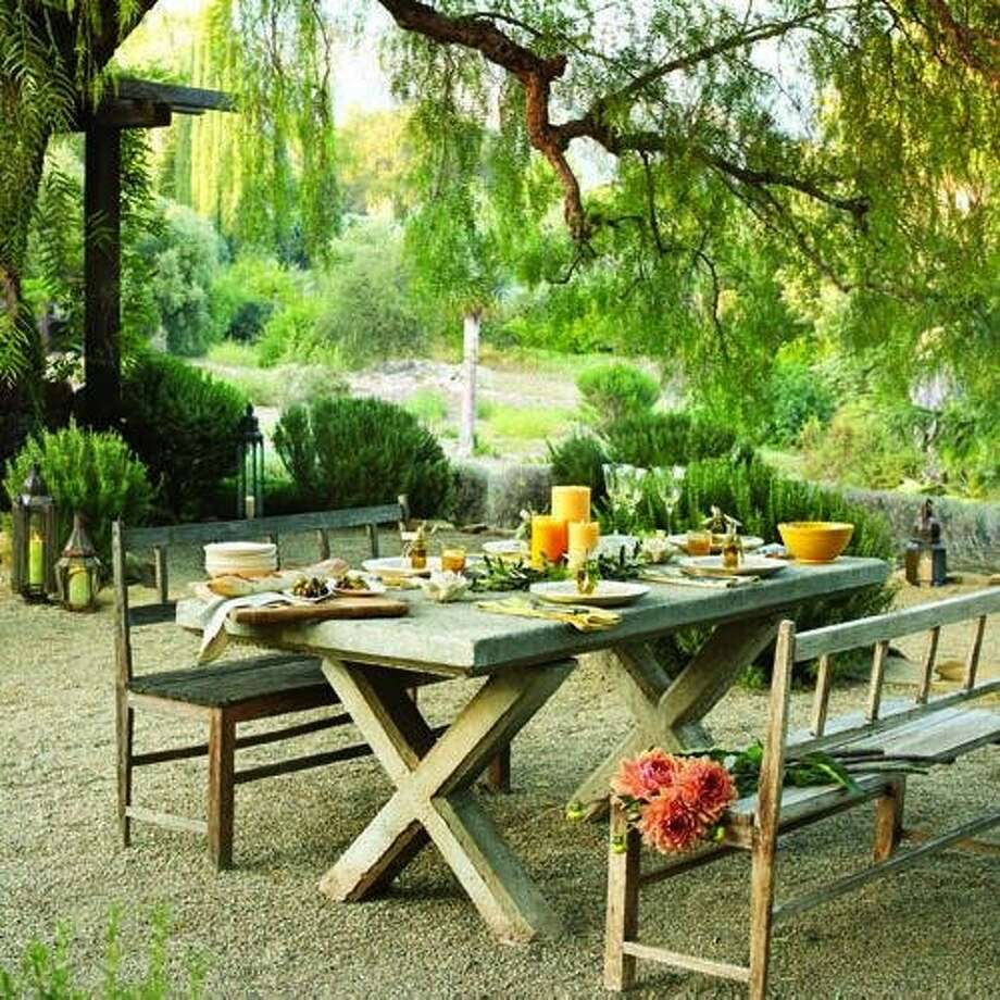 """Tuscan dining: The courtyard: Designer Paul Hendershot calls his Ojai, Calif. garden """"a Mediterranean courtyard without walls.""""  The centerpiece is a concrete-topped table (more on that next slide).  Inspired by the casual elegance of Mediterranean-style gardens, Hendershot carpeted his patio with pea gravel. """"It feels good to walk on when barefoot,"""" he says.   A pepper tree provides light shade on hot days. To complement the tree ― and the garden's overall look ― Hendershot also planted boxwood, 'Provence' lavender, Myrtus communis 'Compacta' (which he likes for its scent), and upright rosemary. Photo: Thomas J. Story, Sunset.com"""