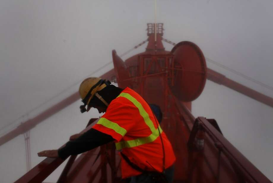 Golden Gate Bridge paint and sandblast crew chief, Tilman Hanson looks over the railing on the top of the south tower of the bridge on May 21, 2012 in San Francisco, Calif. Photo: Mike Kepka, The Chronicle