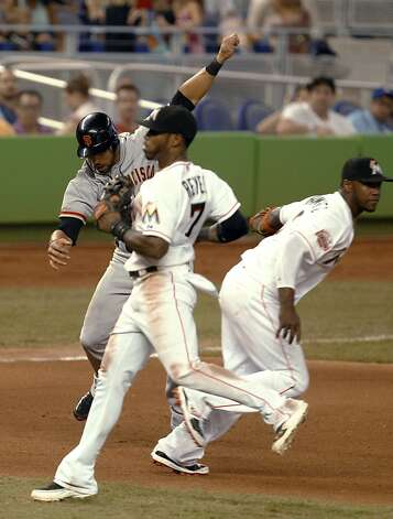 San Francisco Giants' Angel Pagan, left, is tagged out by Miami Marlins third baseman Hanley Ramirez, right, while caught between second and third bases in the seventh inning of a baseball game in Miami, Saturday, May 26, 2012. At center is Marlins shortstop Jose Reyes (7). The Marlins won 5-3. (AP Photo/Lynne Sladky) Photo: Lynne Sladky, Associated Press