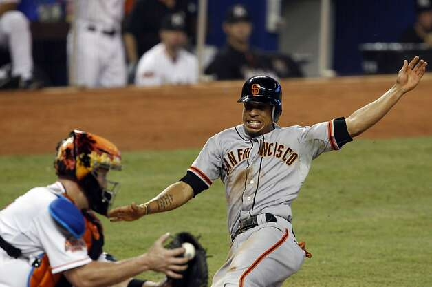 San Francisco Giants' Emmanuel Burriss, right, beats the throw to Miami Marlins catcher John Buck, left, to score in the third inning of a baseball game in Miami, Saturday, May 26, 2012. (AP Photo/Lynne Sladky) Photo: Lynne Sladky, Associated Press
