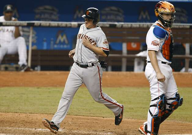 San Francisco Giants' Ryan Theriot, left, scores on a ground out by Melky Cabrera, next to Miami Marlins catcher John Buck, right, during the eighth inning of a baseball game in Miami, Saturday, May 26, 2012. The Marlins defeated the Giants 5-3. (AP Photo/Lynne Sladky) Photo: Lynne Sladky, Associated Press