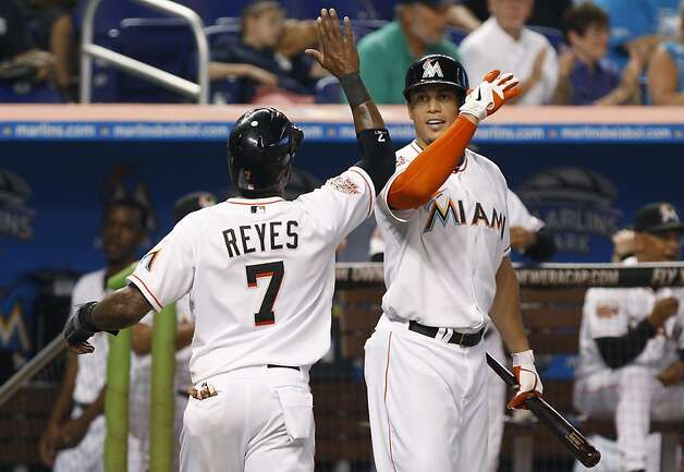 Miami Marlins' Jose Reyes (7) is met by Giancarlo Stanton, right, after scoring on a single by Hanley Ramirez in the third inning during a baseball game against the San Francisco Giants in Miami, Saturday, May 26, 2012. (AP Photo/Lynne Sladky) Photo: Lynne Sladky, Associated Press