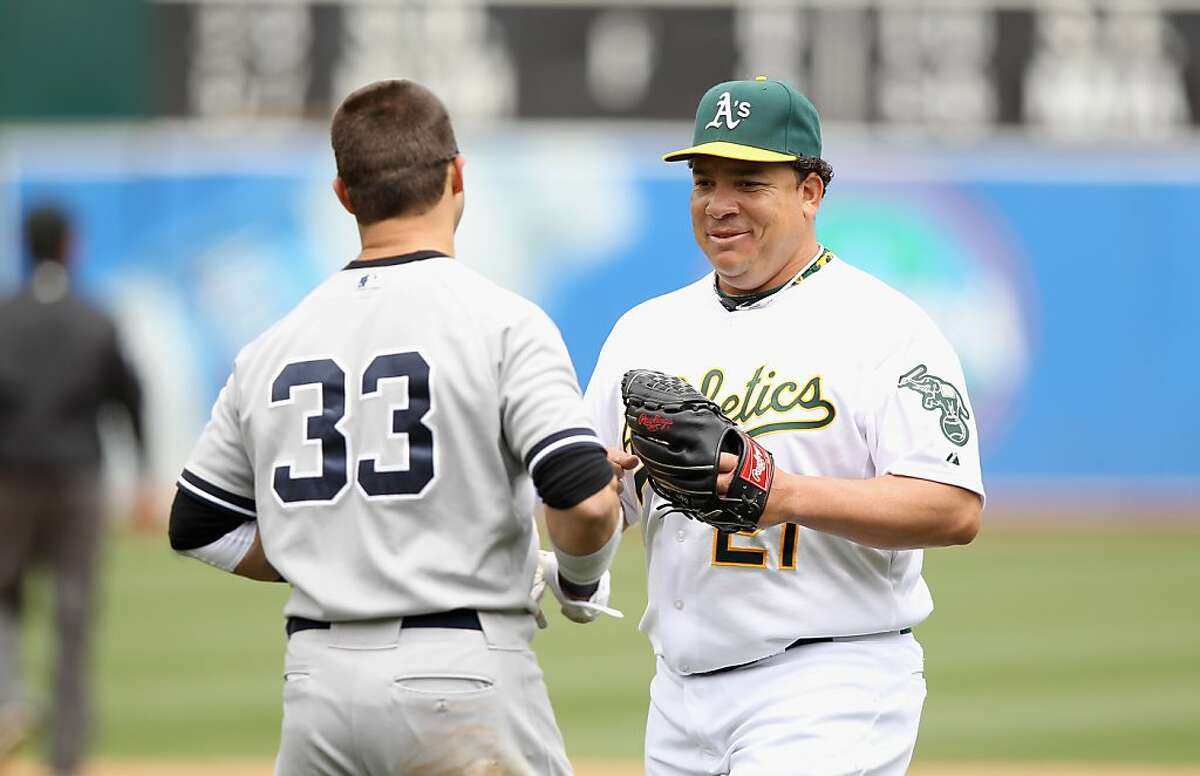 OAKLAND, CA - MAY 26: Bartolo Colon #21 of the Oakland Athletics jokes with Nick Swisher #33 of the New York Yankees after the end of the fourth inning at O.co Coliseum on May 26, 2012 in Oakland, California. Swisher hit a double in the inning. (Photo by Ezra Shaw/Getty Images)