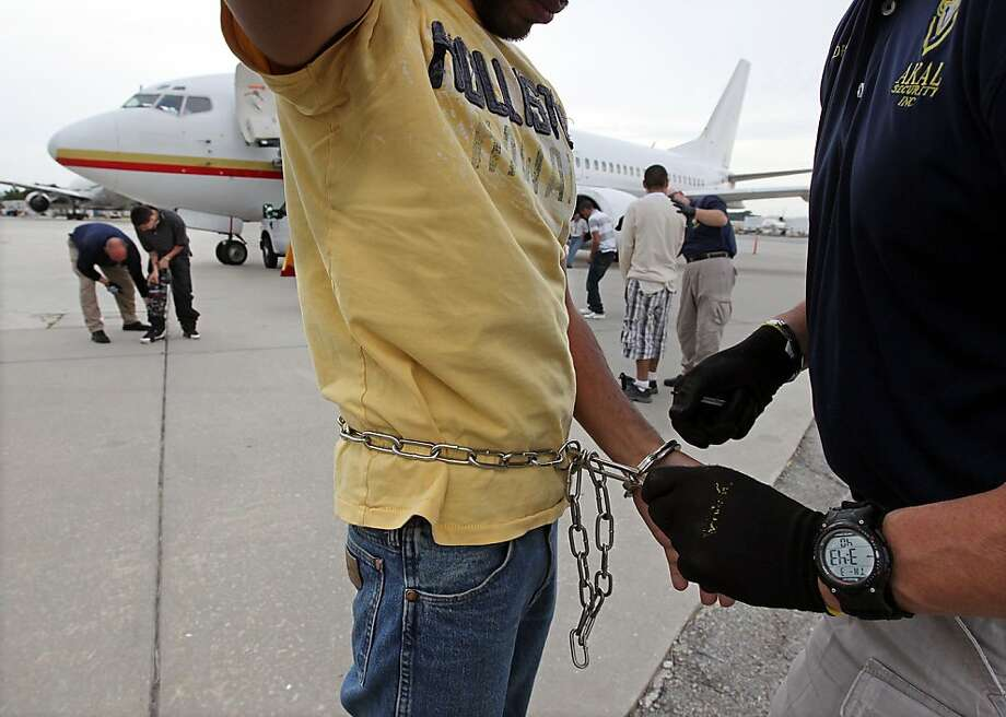ICE officers search illegal immigrants while placing 100 on an ICE deportation flight out of Atlanta to Texas and on to Mexico, May 3, 2012. (Curtis Compton/Atlanta Journal-Constitution/MCT) Photo: Curtis Compton, McClatchy-Tribune News Service