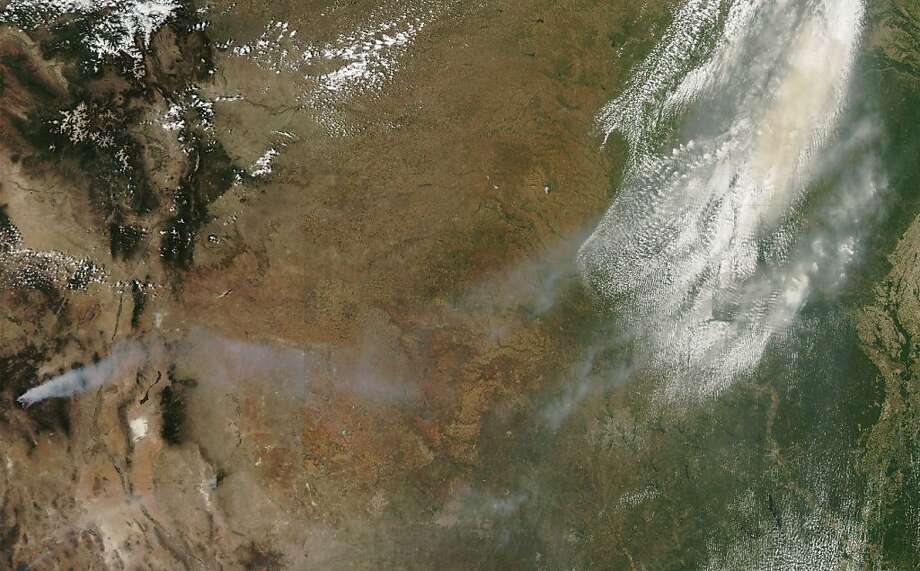 This image provided by NASA shows smoke from New Mexico wildfires drifting across the southcentral United States. The image was acquired Thursday May 24, 2012 by NASA's MODIS satellite Aqua. Firefighters are battling a massive wildfire in southwestern New Mexico that has destroyed a dozen cabins and spread smoke across the state, prompting holiday weekend air-quality warnings. The fire burned early Saturday through remote and rugged terrain around the Gila Wilderness and has grown to 85,000 acres or more than 130 square miles. Fire officials say nearly all of the growth has come in recent days due to relentless winds.  (AP Photo/NASA) Photo: Associated Press
