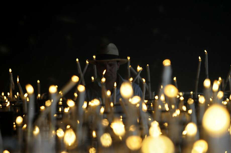 A pilgrim lights candles in the village during the annual El Rocio pilgrimage, on May 26, 2012 in the Rocio, Huelva.The pilgrimage to Almonte which houses the Virgin del Rocio is the largest in Spain with hundreds of thousands of devotees in traditional outfits converging in a burst of colour as they make their way on horseback and decorated carriages across the Andalusian countryside. AFP PHOTO / CRISTINA QUICLERCRISTINA QUICLER/AFP/GettyImages Photo: Cristina Quicler, AFP/Getty Images