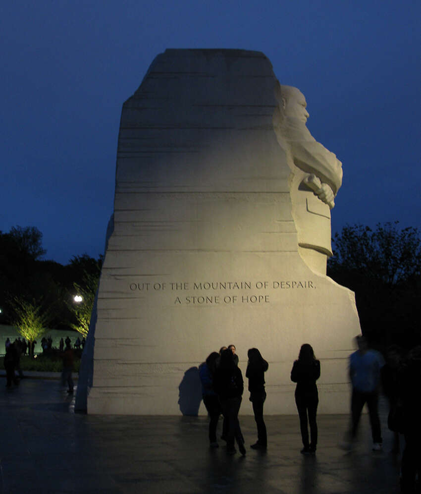 Visitors to the Martin Luther King Memorial pose before and gaze at the part of the exhibit titled