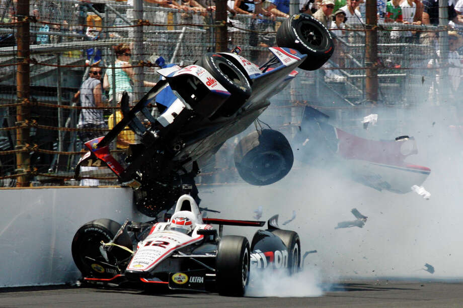 Will Power (12), of Australia, drives under Mike Conway, of England, after they made contact in the first turn during IndyCar's Indianapolis 500 auto race at Indianapolis Motor Speedway in Indianapolis, Sunday, May 27, 2012. (AP Photo/Tom Hemmer) Photo: Tom Hemmer, Associated Press / AP