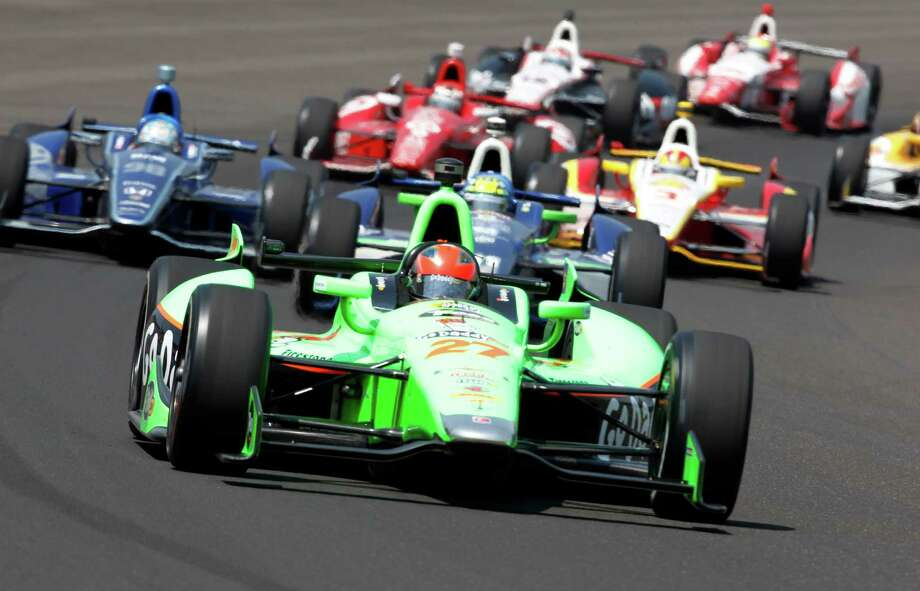 James Hinchcliffe, of Canada, leads a pack of cars trough the first turn during IndyCar's Indianapolis 500 auto race at Indianapolis Motor Speedway in Indianapolis, Sunday, May 27, 2012. (AP Photo/Tom Strattman) Photo: Tom Strattman, Associated Press / FR29600 AP
