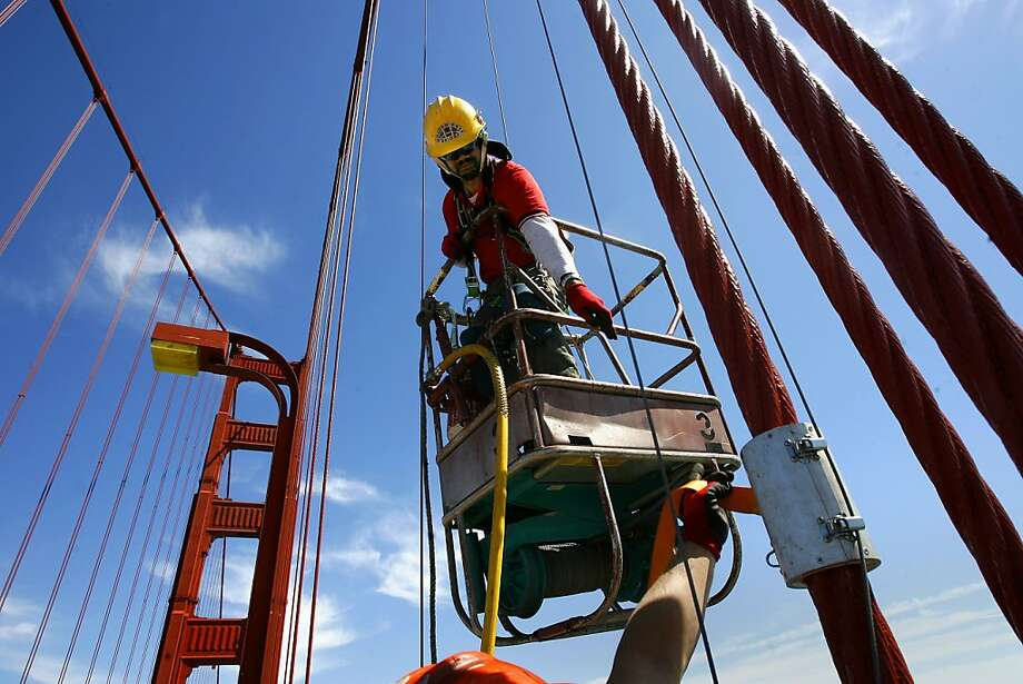 """Bridge painter, Herbert Gabriel uses a basket called a """"Spider"""" to move up and down the suspension cables for maitenance work and painting. Photo: Michael Macor, The Chronicle"""