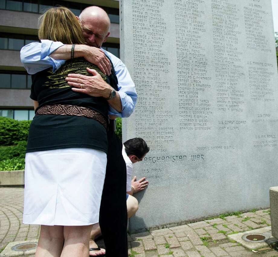Christian Bill touches his brother's name as Michael Parry hugs his wife, Patricia, after the incription of their son, Navy SEAL Brian Bill, was unveiled on the memorial wall at Veteran's Park after Stamford's Memorial Day Parade in Stamford, Conn., May 27, 2012. Bill was killed along with 29 other Americans and eight Afghan commandos when the double-rotor Chinook helicopter taking them into a hot combat zone to reinforce coalition troops was hit by a Taliban fighter's rocket-propelled grenade. The Aug. 6 crash was the single deadliest day for American forces in Afghanistan since the war began in 2001. This is the first Memorial Day since his death. Photo: Keelin Daly / Stamford Advocate
