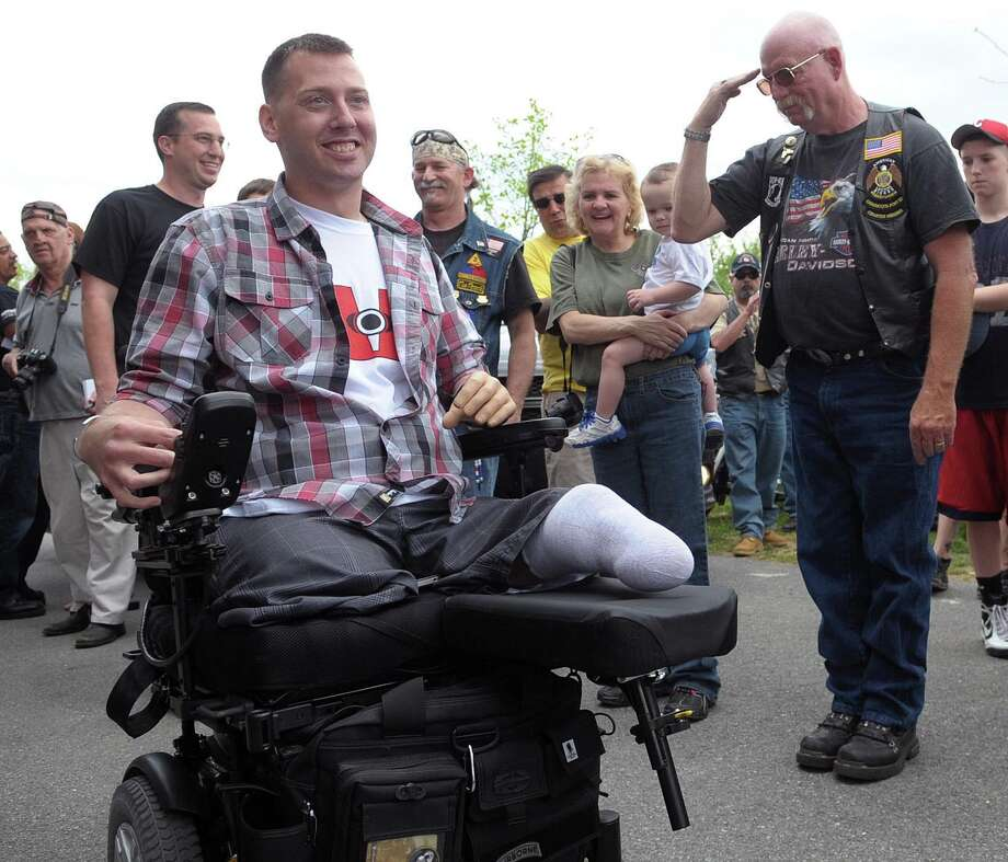 U.S. Army Sgt. Adam Keys, wounded in Afghanistan in 2010, is greeted by community members in Whitehall Township, Pa., in April. Almost half of the 1.6 million veterans from the wars in Iraq and Afghanistan are now seeking compensation for their disabilities, that's more than double the rate of the Gulf War. Photo: Matt Smith / AP2012