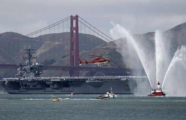 The fireboat Guardian welcomes the Nimitz, one of world's largest warships, after the Navy aircraft supercarrier sails under the Golden Gate Bridge to celebrate the bridge's 75th anniversary. Photo: Paul Chinn, The Chronicle
