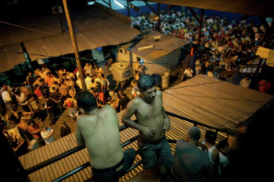 Inmates gather outside their cells in San Pedro Sula Central Corrections Facility. Inside one of Honduras' most dangerous and overcrowded prisons, inmates operate a free-market bazaar. Photo: Rodrigo Abd / AP