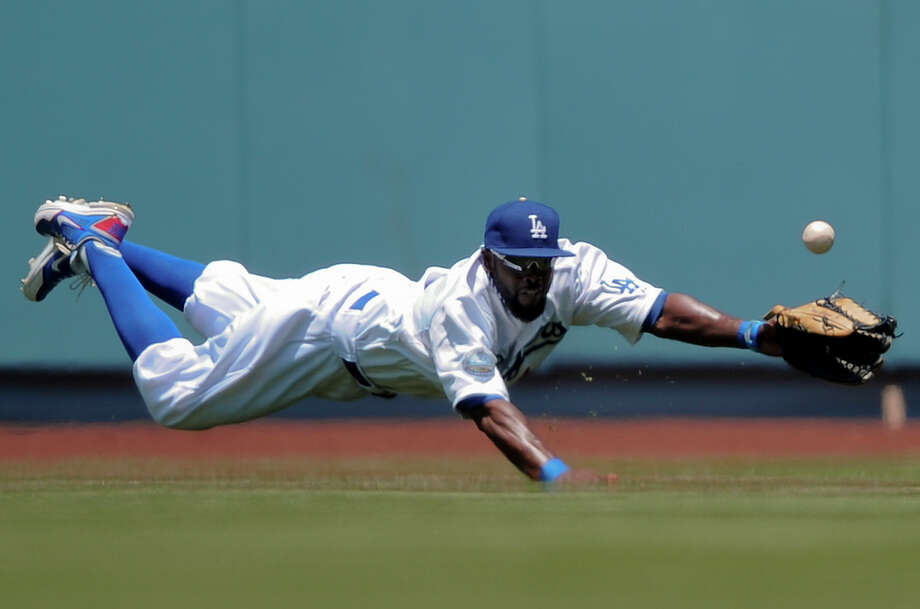 Los Angeles Dodgers center fielder Tony Gwynn is unable to get to a ball hit by Houston Astros' Jose Altuve, giving up a triple, in the first inning of a baseball game on Sunday, May 27, 2012, in Los Angeles. (AP Photo/Gus Ruelas) Photo: Gus Ruelas, Associated Press / FR157633 AP
