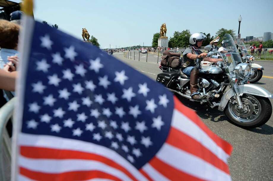 People wave US flags as riders on their motorbikes roar past during the Rolling thunder demonstration in Washington, DC, on May 27, 2012. The 25th Annual Rolling Thunder rumbled into town to show support for veterans past and present, those who have fallen in war and those who are missing in action.  It's expected nearly one million riders will be here through Memorial Day. Photo: JEWEL SAMAD, AFP/Getty Images / AFP