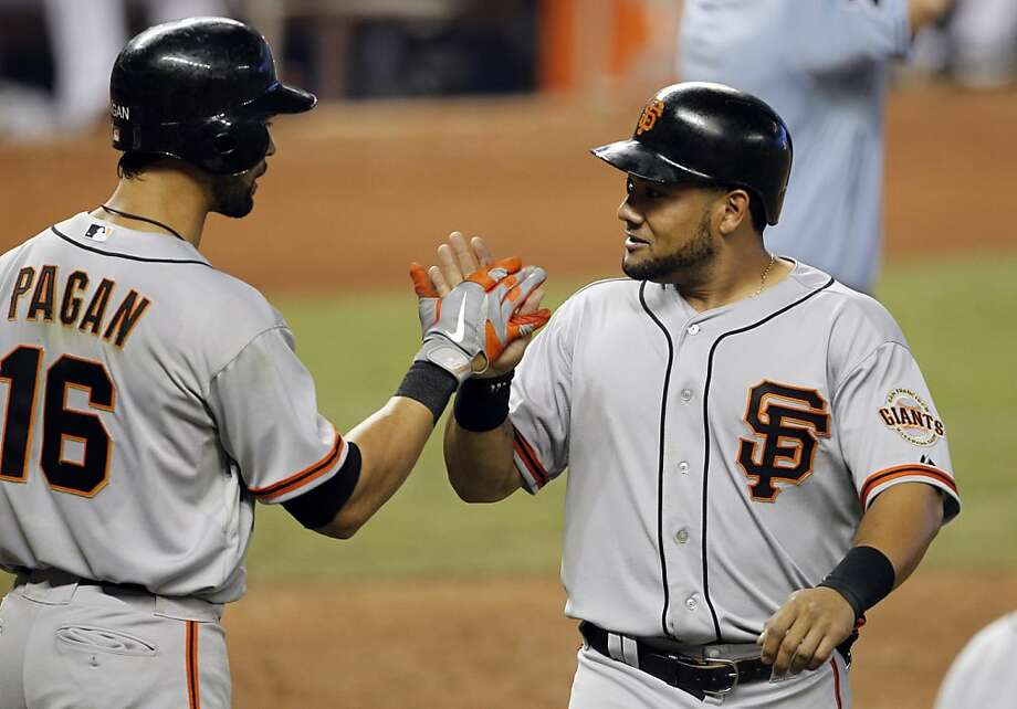 San Francisco Giants' Melky Cabrera, right, is met by teammate Angel Pagan (16) after scoring on a double by Buster Posey in the sixth inning of  a baseball game against the Miami Marlins in Miami, Sunday, May 27, 2012. (AP Photo/Lynne Sladky) Photo: Lynne Sladky, Associated Press