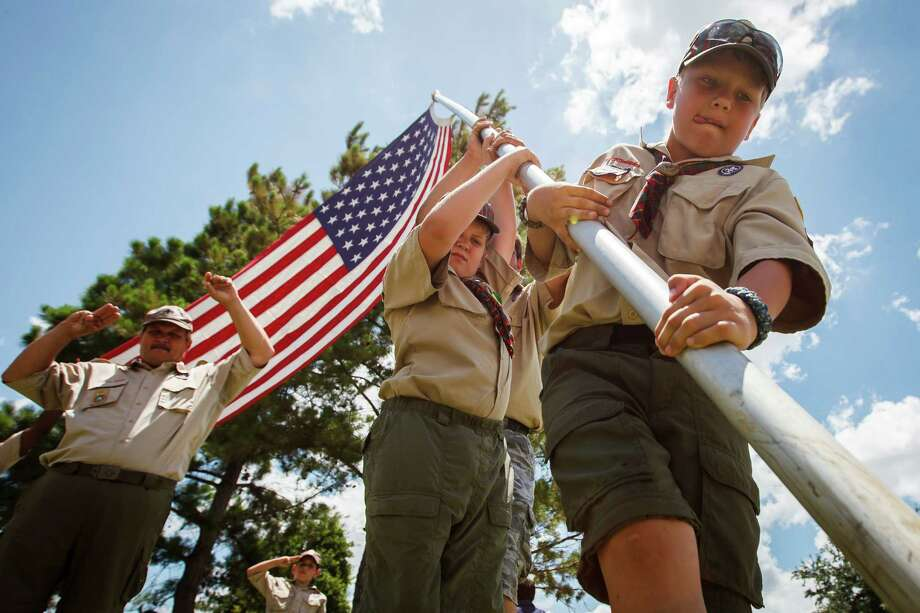 Mitchell Valentine, 10, right, and Brandon Liske-Womack, 10, second from right, of Boy Scout Pack 824 raise a flag at the Houston VA National Cemetery, Sunday, May 27, 2012, in Houston.  Over 229 flags were raised in honor of the upcoming Memorial Day Service. Photo: Michael Paulsen, Houston Chronicle / © 2012 Houston Chronicle