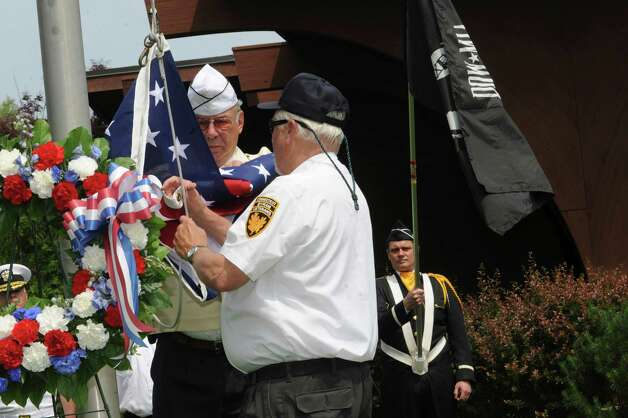Byram veterans past commanders Don Merchant, left, and Joe Kralik raise the American flag at the ceremony during the Byram Veterans Association's annual Memorial Day parade on Sunday, May 27, 2012. Photo: Helen Neafsey / Greenwich Time