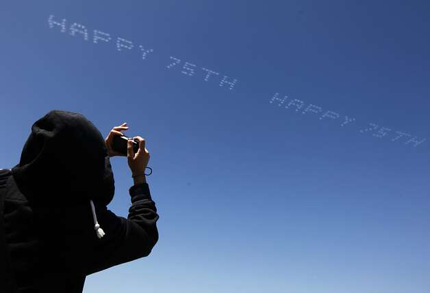 Sarah Ho snaps photos of a message in the sky above the 75th anniversary celebration for the Golden Gate Bridge in San Francisco, Calif. on Sunday, May 27, 2012. Photo: Paul Chinn, The Chronicle