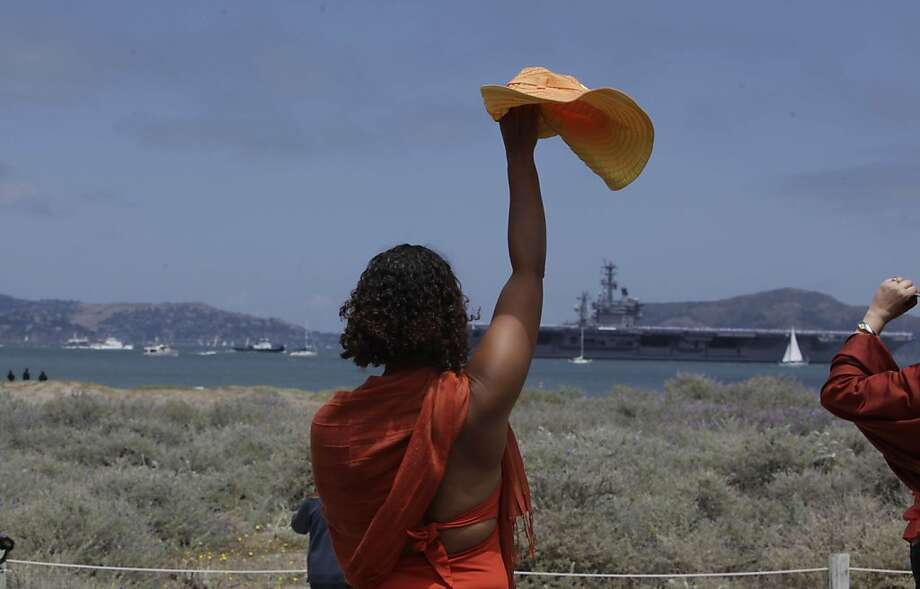 Kim Sykes of San Francisco waves her hat as the USS Nimitz passes on the bay during the Golden Gate Festival celebrating the Golden Gate Bridge's 75th anniversary at Crissy Field  on Sunday, May 27, 2012 in San Francisco, Calif. Photo: Lea Suzuki, The Chronicle