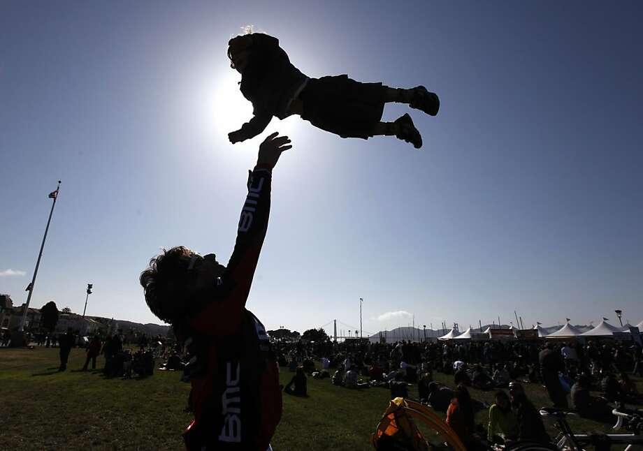 Pascal Molat, a principal dancer with the San Francisco Ballet, tosses and catches his son Matisse, 2, on the Marina Green during the anniversary celebration, which drew thousands of well-wishers. Photo: Paul Chinn, The Chronicle