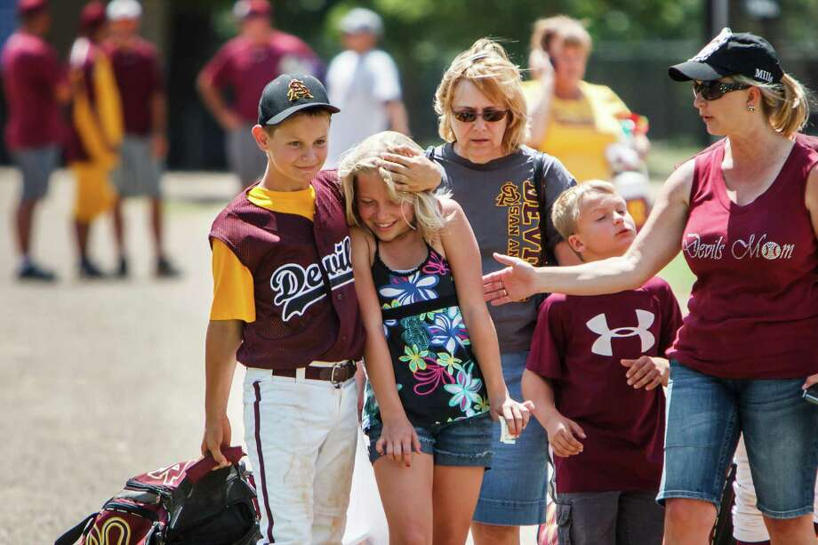 Tayler Mills, 11, left, gives a squeeze to Dakota Timmermann, 13, after finishing his baseball game in the Texas Invitational at Doss Park, Sunday, May 27, 2012, in Houston. ( Michael Paulsen / Houston Chronicle ) Photo: Michael Paulsen / © 2012 Houston Chronicle