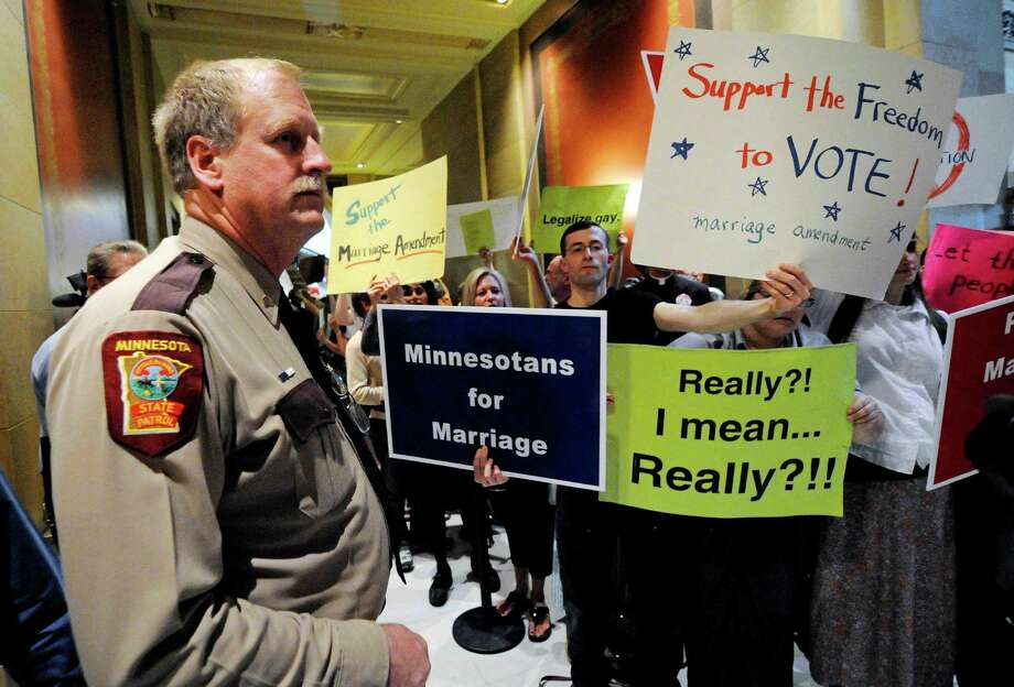 Protestors represent both sides of the gay marriage debate in Minnesota, one of four states voting on the issue in November. Gay marriage has been rejected by voters in 32 states, even as polls show public support growing. Photo: Jim Mone / AP