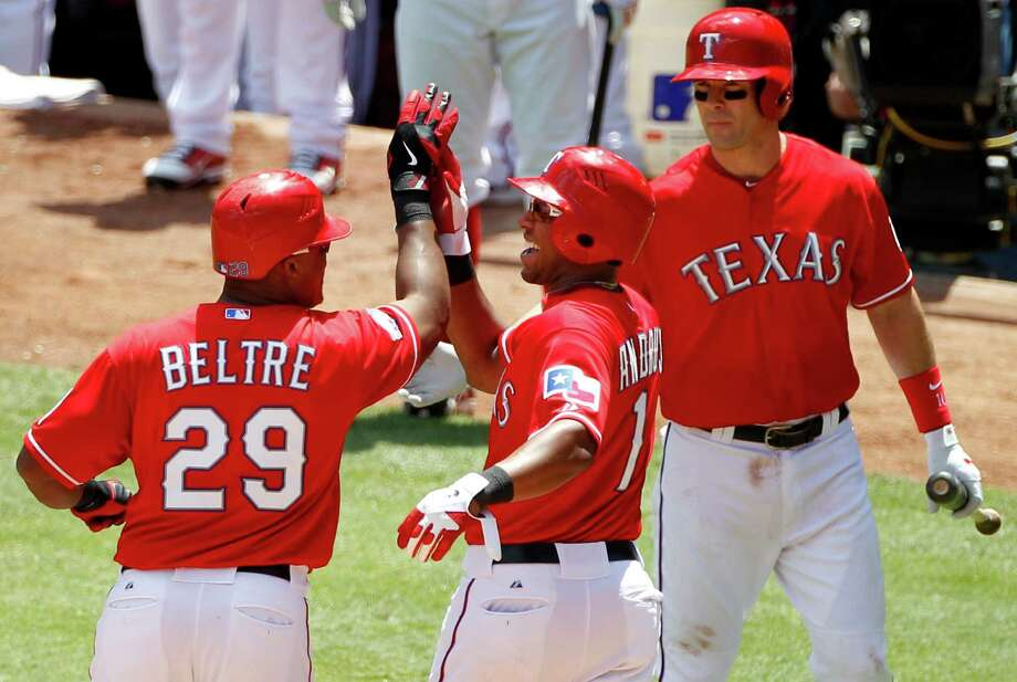 Texas Rangers' Adrian Beltre (29) is congratulated by teammates Elvis Andrus (1) and Michael Young, right, following his two-run home run that also scored Andrus off a pitch from Toronto Blue Jays' Kyle Drabek in the second inning of a baseball game on Sunday, May 27, 2012, in Arlington, Texas. The Rangers won 12-6. Photo: AP