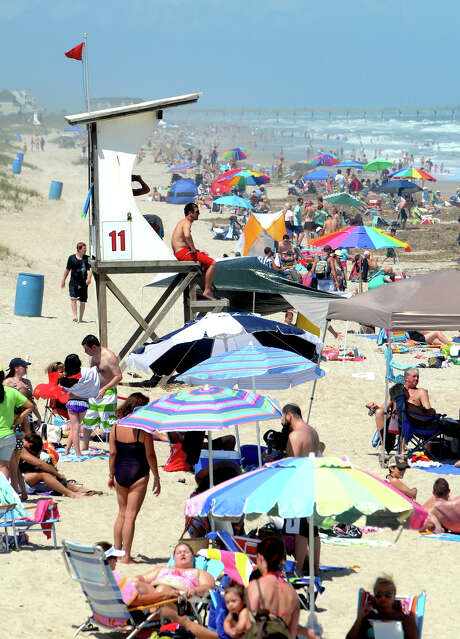 People crowd Wrightsville Beach in Wilmington, N.C., on Sunday as red flags fly warning swimmers of dangerous conditions and rip currents due to Tropical Storm Beryl. The National Hurricane Center said Beryl was nearing hurricane strength. Photo: Jeff Janowski / The Star-News