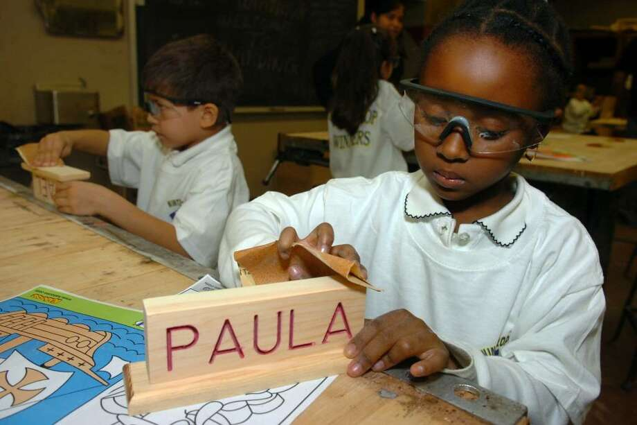 Paula Calisme, a first grader from Winthrop School, uses sandpaper to smooth a pencil holder with her name on it, crafted in the wood shop at Harding High School, in Bridgeport, Conn. Nov. 23rd, 2009. Photo: Ned Gerard / Connecticut Post
