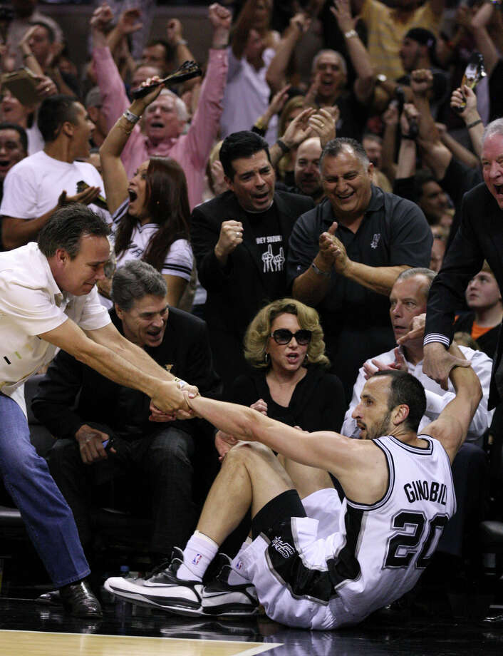 Texas Gov. Rick Perry, left, cheers as San Antonio Spurs' Manu Ginobili (20) is helped off the court after hitting a three point basket during the first half of game one of the NBA Western Conference Finals in San Antonio, Texas, Sunday, May 27, 2012. Pictured at bottom center is Julianna Holt, wife of Spurs owner Peter Holt. Seated next to Julianna Holt is Lt. Gov. David Dewhurst and at far right, helping Ginobili up,  is Peter Holt. Photo: Edward A. Ornelas, Express-News / © 2012 San Antonio Express-News