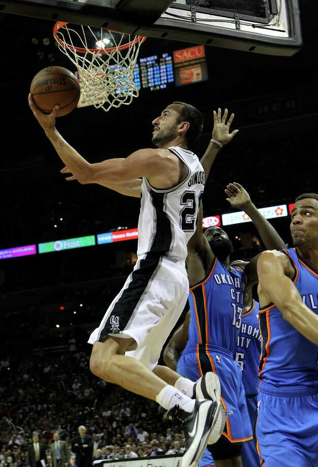 San Antonio Spurs' Manu Ginobili (20) lays the ball in against Oklahoma City Thunder's Thabo Sefolosha, right, during the second half of game one of the NBA Western Conference Finals in San Antonio, Texas on Sunday, May 27, 2012. Photo: Kin Man Hui, Express-News / © 2012 San Antonio Express-News